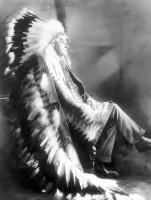 President Calvin Coolidge, wearing a gift, a Sioux headdress.