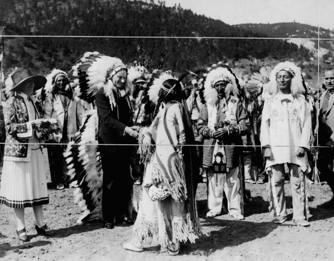 "Marked for cropping, this photograph was taken upon President Coolidge's honorary induction into the Sioux, 1927. Dubbed Wamble-To-Ka-Ha (Chief ""Leading Eagle""), Coolidge also accepted the ceremonial headdress he is wearing. One of the Sioux chiefs said to Coolidge, ""They tell us you are the thirtieth President of this great country, but to us you are our first President."""