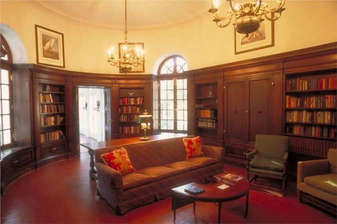 The library where President and Mrs. Coolidge had their portraits painted. The background for the First Lady's portrait is the picturesque Spanish moss and green lawns of this, as with so many, Southern mansions.