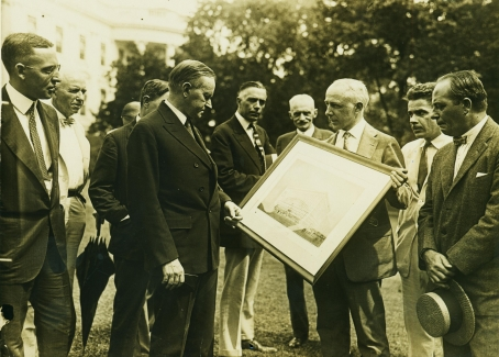 President Coolidge, on the White House grounds, reviews plans for the National Press Building later that same year, September 15, 1925.