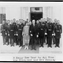 President and Mrs. Coolidge with military aides, just after they assisted in a New Year reception, posed outside the White House 1-1-1927