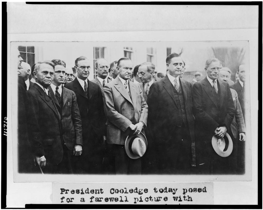 Coolidge standing for the farewell picture with White House correspondents, February 26, 1929.
