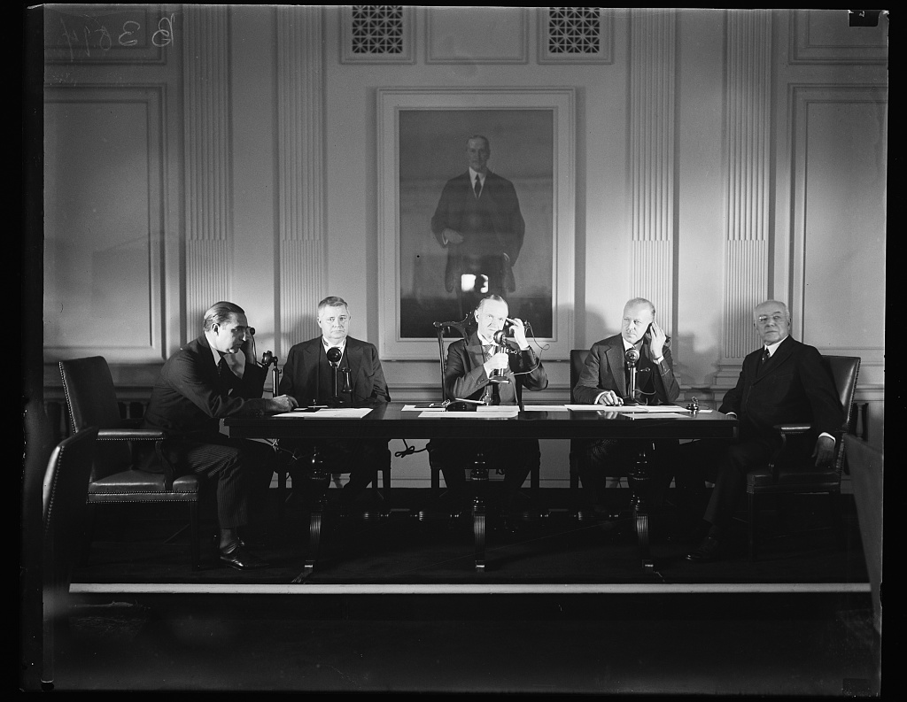 Pictured here in the Chamber of Commerce Building in Washington, D.C., from L to R: Don Mariano de Amoede y Galaremendi (Spanish Embassy, Washington); Under Secretary of State J. Reuben Clark; President Coolidge, speaking to King Alfonso; Walter S. Gifford, president of AT & T; and Joseph H. De Frees, chairman of the board, U.S. Chamber of Commerce. The man in the portrait above them is businessman Harry A. Wheeler, the first chairman of the U.S. Chamber of Commerce.