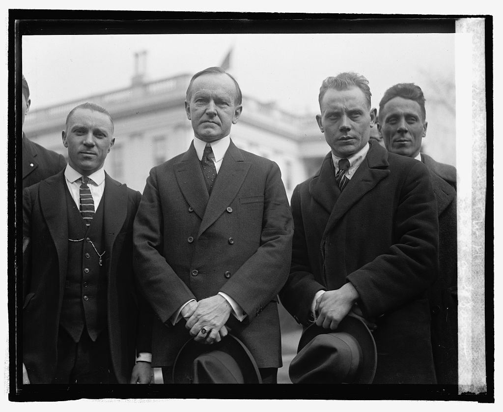 "American track runner and Olympic bronze winner Joie Raye (L of Coolidge) and Paavo Nurmi of Finland (R), who would win his ninth gold medal at the Olympics in 1928 in long distance running. Raye and Nurmi (the ""Flying Finn"") visited President Coolidge at the White House on February 21, 1925."