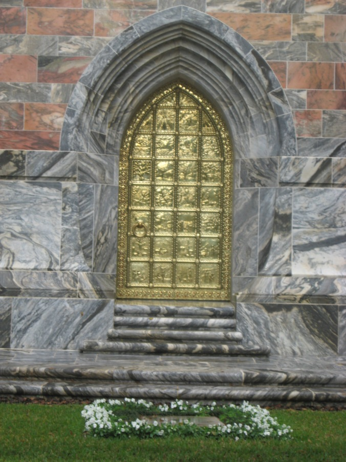 The Golden Door on the north side of the Tower, depicting the Creation and Fall of Man. Mr. Bok's grave lies at the foot of the stairs, surrounded by white flowers.