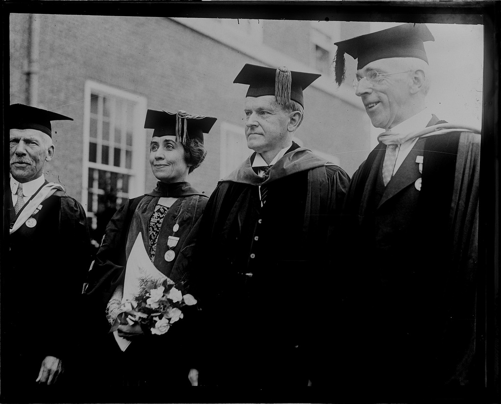 The Coolidges, both college graduates, in cap and gown during their visit to the 150th Anniversary of Phillips Academy. To their right stands the Headmaster, Alfred Stearns, to their left, Alfred L. Ripley (believe it or not).