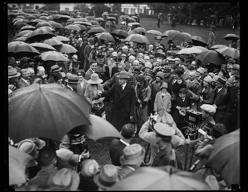 Overruling his own doctor, President Coolidge ventures out in the rain to greet the thousands of doctors gathered at the White House the day after his speech to these professionals in Washington for the American Medical Association's Annual Session, May 18, 1927.