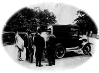 Mail truck is loaded with the Declaration and Constitution as Herbert Putnam, wearing the fedora, supervises the transfer to the Library.