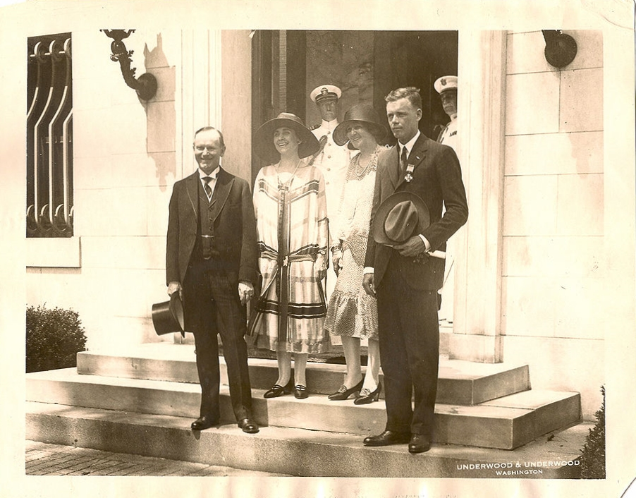 Lindbergh and his mother hosted by the Coolidges at DuPont Circle, where the President and his wife stayed during repairs to the White House roof that spring. Notice how everyone is cheerful except the unexpectedly sober figure on the right. Lindbergh, about to appear in a light suit, was corrected by Coolidge who chose a dark suit for him as better befitting the formality of the occasion. Even returning heroes need to take care of the way they dress. They set a deeper example than they may realize, one  that should not be treated flippantly.