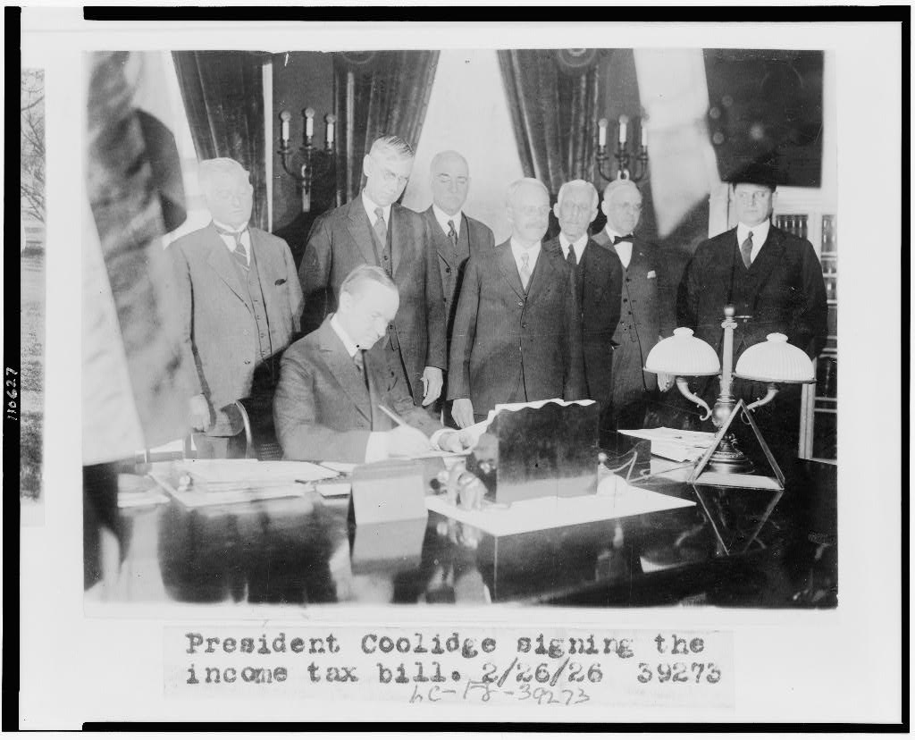 The President signs the Revenue Act, 1926. To the left of the legislators stands Secretary Mellon, Director Herbert M. Lord and Everett Sanders, all the right of the photo. Courtesy of the Library of Congress.