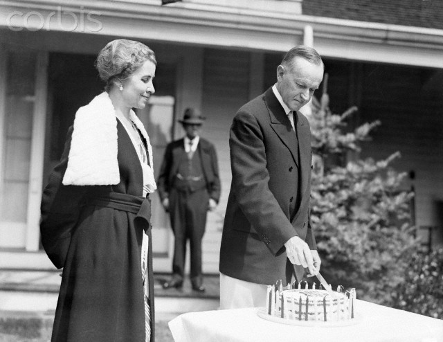 Coolidge cuts the cake made for his 59th birthday, as Grace beams, at the Stearns' home in Swampscott, Massachusetts, July 1931.