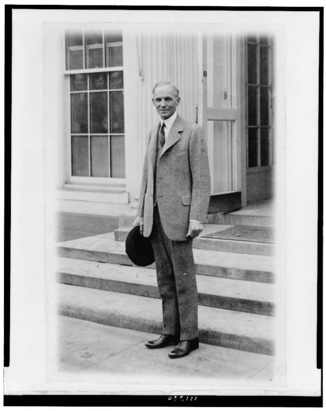 Henry Ford, after meeting with President Coolidge, 1927. Do you see the three faces peering out the window as the photographer snaps this picture? Courtesy of the Library of Congress.