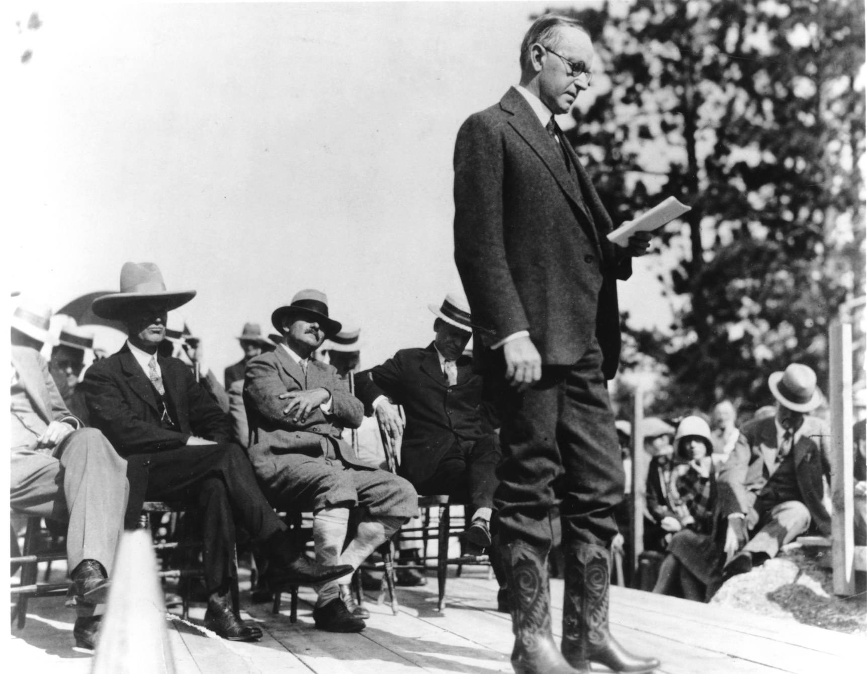 President Coolidge dedicates the site that will be the Mount Rushmore Memorial, August 10, 1927. Flamboyant sculptor, Gutzon Borglum is seated cross-legged directly behind the standing President.