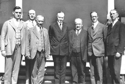Coolidge meeting with a Knights of Columbus delegation there to discuss religious freedoms in Mexico, at the summer White House, Adirondacks, 1926. From L to R, they are: Pictured left to right are Supreme Advocate Luke E. Hart, Deputy Supreme Knight Martin Carmody, Supreme Knight James A. Flaherty, President Coolidge, Supreme Secretary William J. McGinley, Supreme Director William C. Prout, and Assistant Supreme Secretary John Conway.