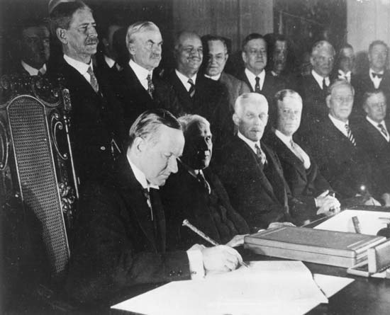 President Coolidge signs the Kellogg-Briand Pact, January 17, 1929, East Room of the White House.