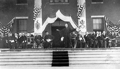 "Here is a scene from the commencement in 1923. When Governor Coolidge spoke to those gathered on these grounds five years before, the men of Holy Cross had already proven to be an expression of patriotic duty, as many of those who would have graduated sooner, were among the first to volunteer for military service. Not only this, however, the young men to whom Coolidge directed his address that summer of 1919 did not all spring from long-established families, but mirrored the rich differences and opportunities America has made possible for everyone. Most of the young men Coolidge addressed were from Irish, Italian, French, Slavic, and even Lithuanian roots. Coolidge, keenly aware of both the College's excellent past and accomplished present, saw America in miniature. This great success was not an anomaly, it was the norm because here freedom and opportunity came not through ancestry or blood but through diligence and perseverance, competence and ability. Having taken up the full burden of citizenship, the young men of Holy Cross demonstrated what it means to know (as Coolidge would express it years later) the ""high estate"" of American citizenship, ""the peer of kings."""