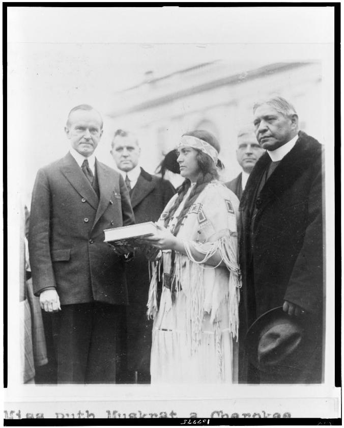 Miss Ruth Muskrat, a Cherokee Indian, presents Mr. Coolidge with a copy of The Red Man in the United States, a survey of the present day American Indian 12-13-1923