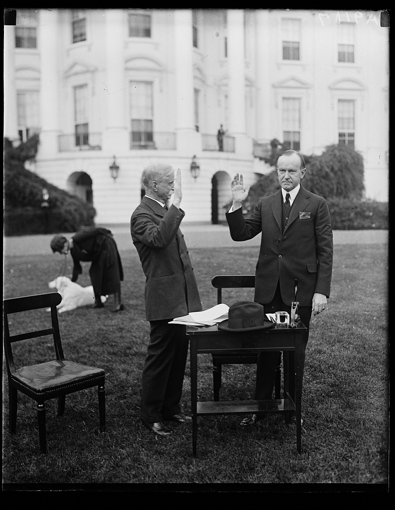 District of Columbia Circuit Judge Josiah A. Van Orsdel, functioning as a polling judge, administers oath to this famous voter, Calvin Coolidge, 1924. The Coolidges would vote by absentee ballot that year since national responsibilities kept them out of their home precinct in Massachusetts. They still made a point of leading by example, however.