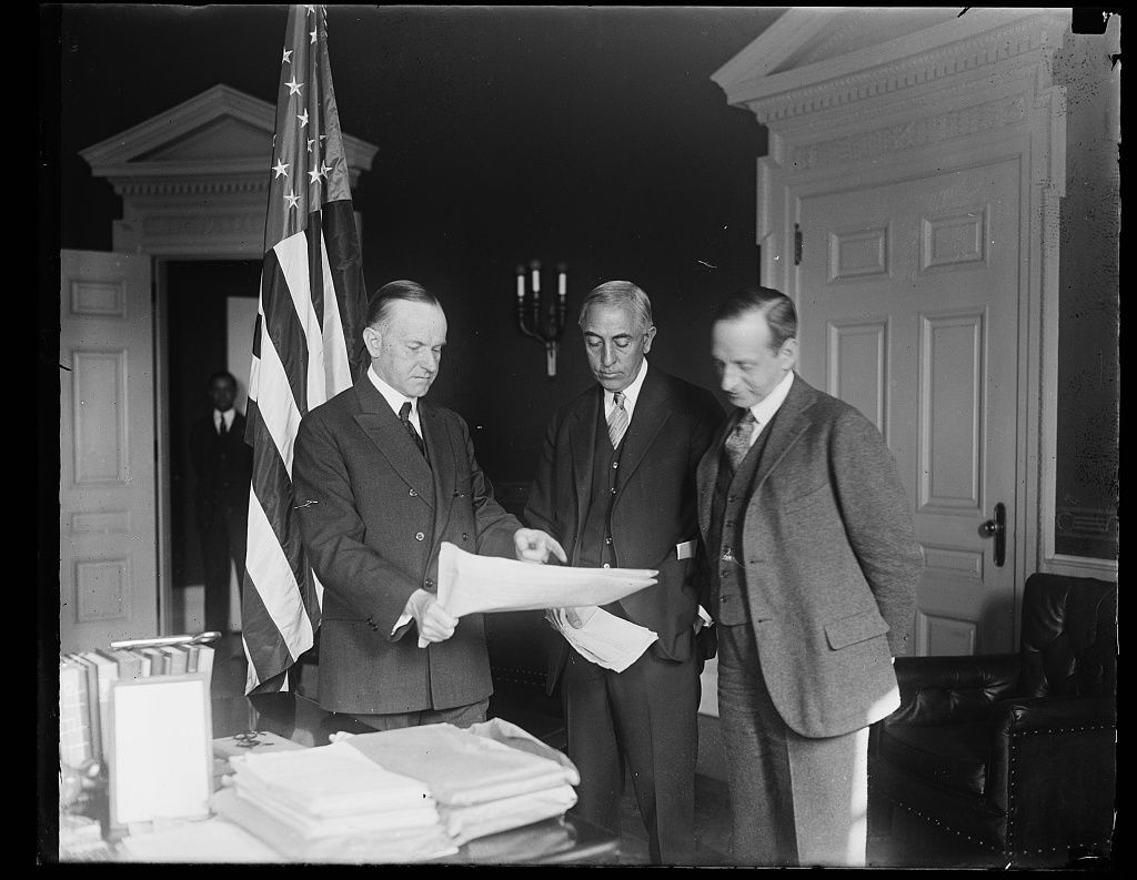 "President Coolidge reviewing official papers with C. Bascom Slemp, his official secretary, and ""Ted"" Clark, his personal secretary since coming to Washington in 1921. Courtesy of the Library of Congress."