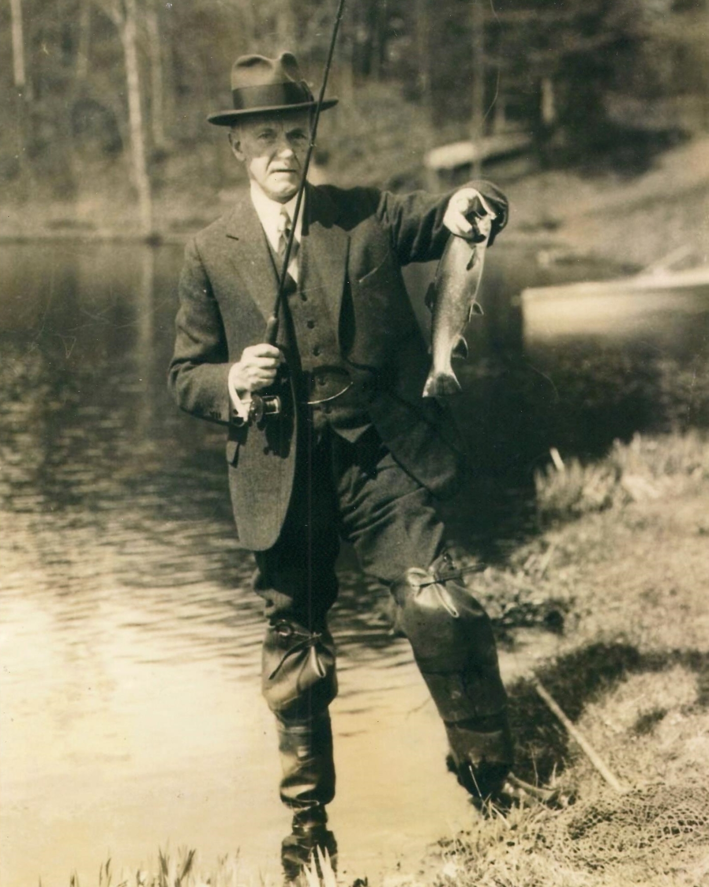 Coolidge held scrupulously to accurate fish stories. He made a point of displaying what he had caught, even documenting it for verification. Here he holds his latest catch up for visual confirmation.