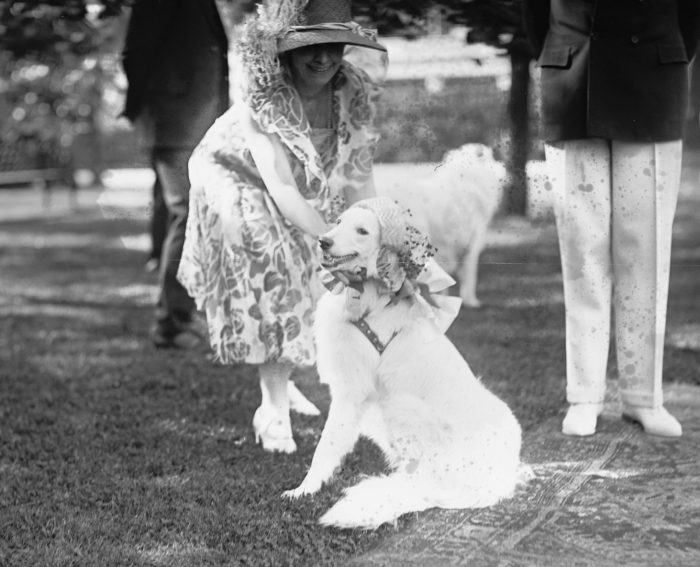 First Lady Grace Coolidge dressing Prudence Prim in her garden party bonnet for the veterans on the White House lawn.