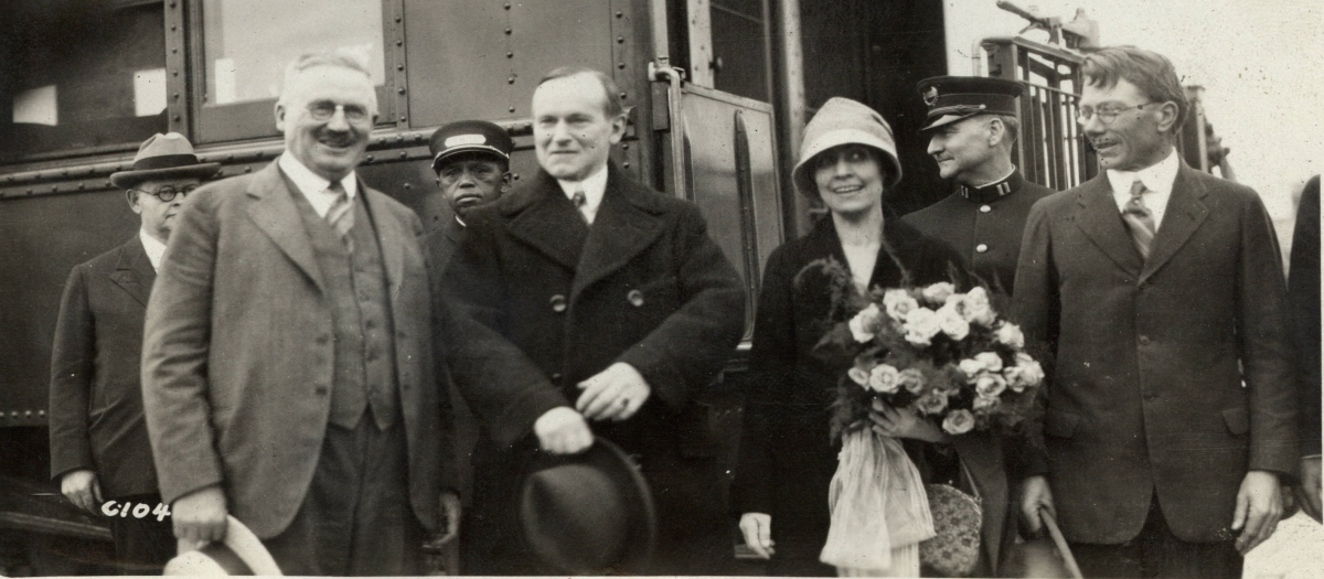 The Coolidges arrive in Rapid City, South Dakota, late afternoon on June 15, 1927. Here they are welcomed by Senator Norbeck (left) and Representative Williamson (right).
