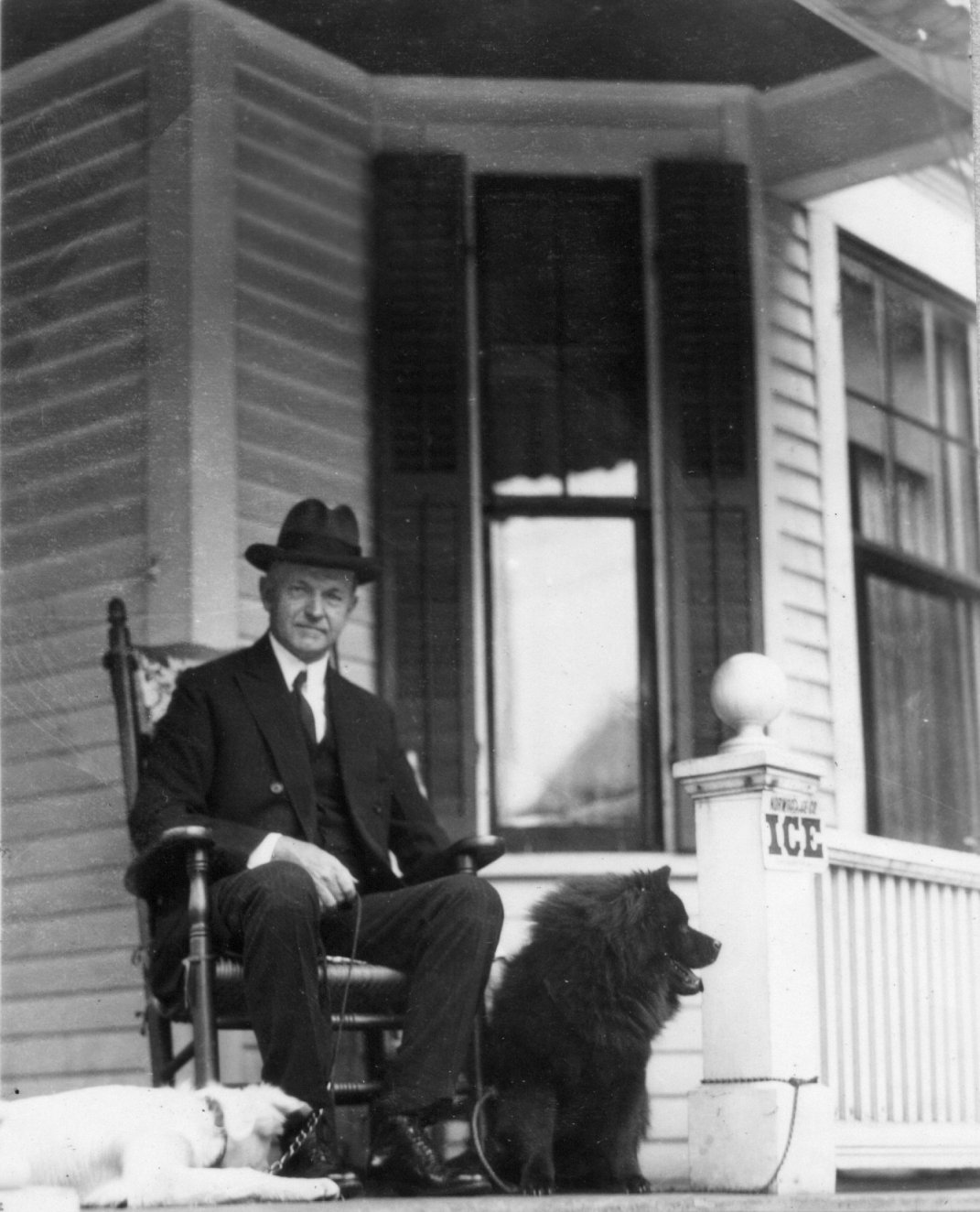 Coolidge, enjoying retirement from public life, with his dogs on the front porch of their first home, 21 Massasoit Street, Northampton, Massachusetts.