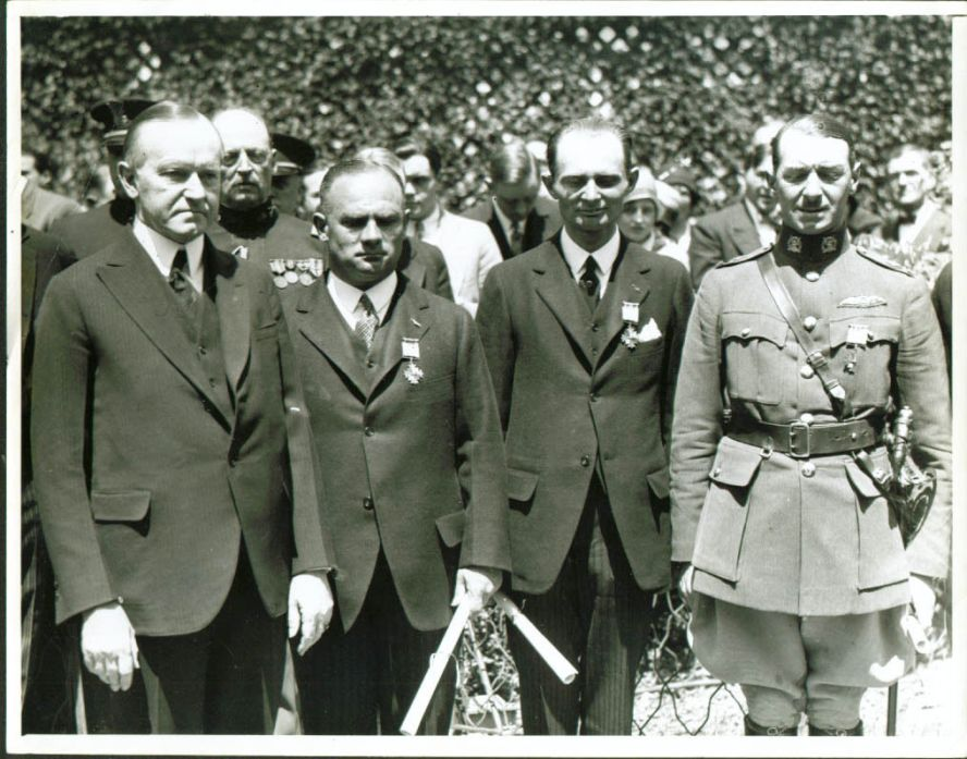 "President Coolidge honoring the aviation pioneers of the Junker ""Bremen"" for the first East to West transatlantic crossing accomplished in April 1928. Here the crew, L to R: Captain Hermann Kohl, Baron von Huenefeld (both of Germany), and Major James C. Fitzmaurice of Ireland, are bestowed the Distinguished Flying Cross, the highest award in aviation, by President Coolidge at the White House, May 1928."