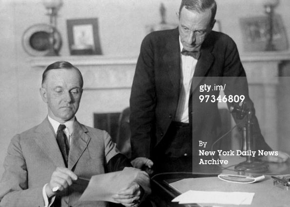 president-calvin-coolidge-penning-his-first-official-public-document-while-his-private-secretary-clark-watches-8-5-1923
