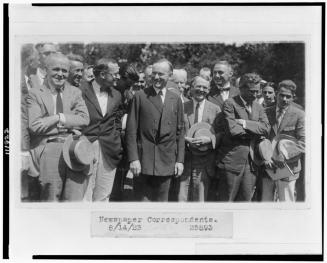 President Coolidge standing with newspaper correspondents on lawn of the White House 8-14-1923