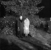 24 Dec 1927, Washington, DC, USA --- 12/24/1927-Washington, DC- Photo shows the President and Mrs. Calvin Coolidge (Mrs. Grace Coolidge), standing in front of the national Christmas tree, lit by the President, officially starting the Christmas holidays in the nation. --- Image by © Bettmann/CORBIS