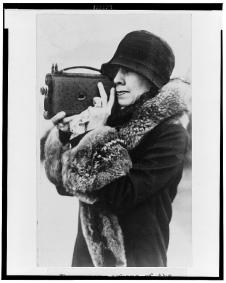 Mrs. Coolidge, member of the White House News Photographers Association, half-length portrait, standing, facing left, holding camera up to face 2-9-1929